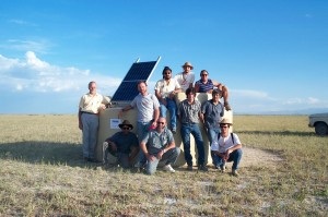 A group of collaborators install the first water detector tank and solar panel