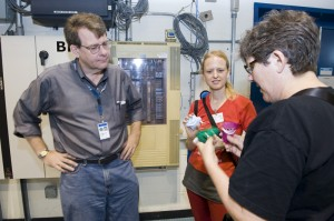 Mike Lindgren, Fermilab's acting deputy head of Particle Physics Division and CDF department head, shows Julie Peasley how particles get detected in a scintilate panel.
