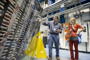 Mike Lindgren of CDF, Julie Peasley and Heidi Schellman of DZero look at the opened CDF detector at Fermilab.
