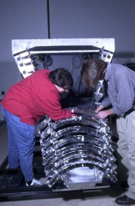 Researchers assemble one of eight detector segments for installation in the ferris wheel-shaped G-Zero apparatus.