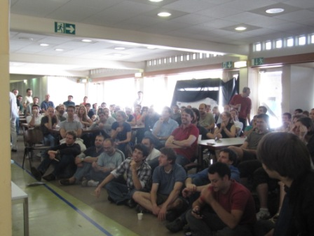 World Cup fans cram into the CERN cafeteria, even sitting on the floor, to get a seat where they can see the game.