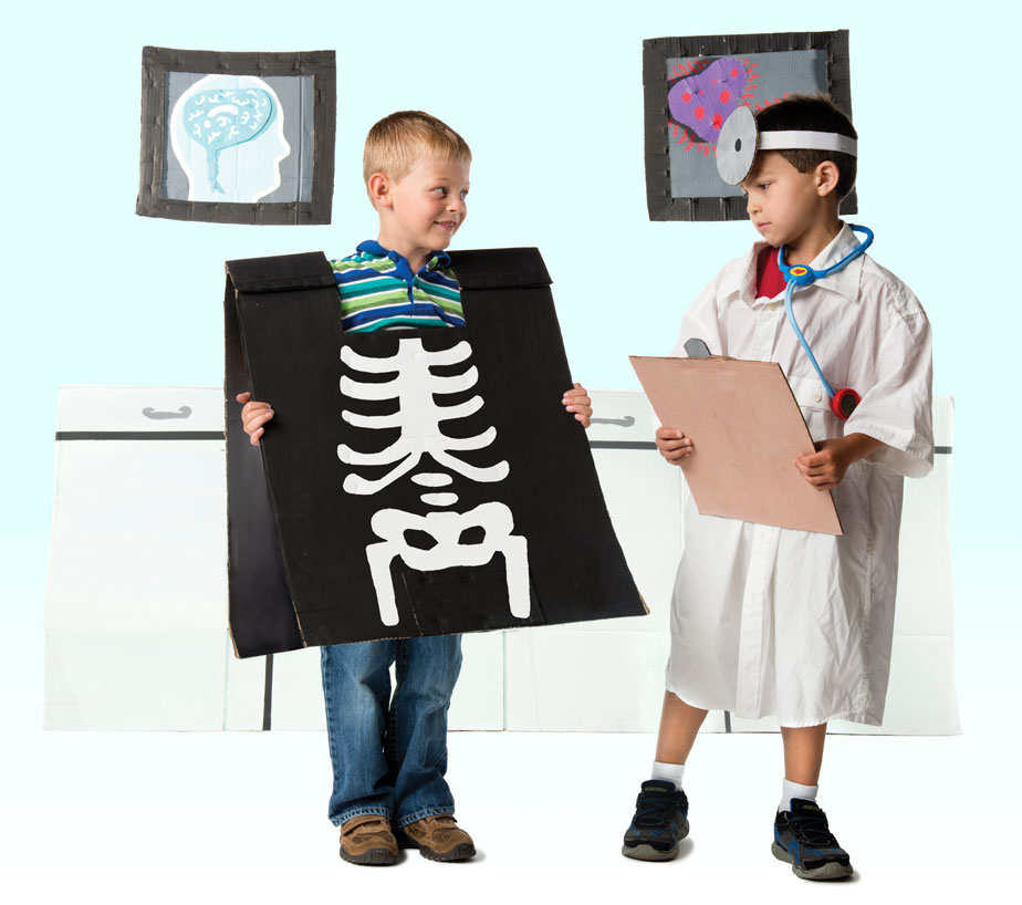 Photo of two children playing with cut-outs of x-rays and doctor's supplies in doctors office