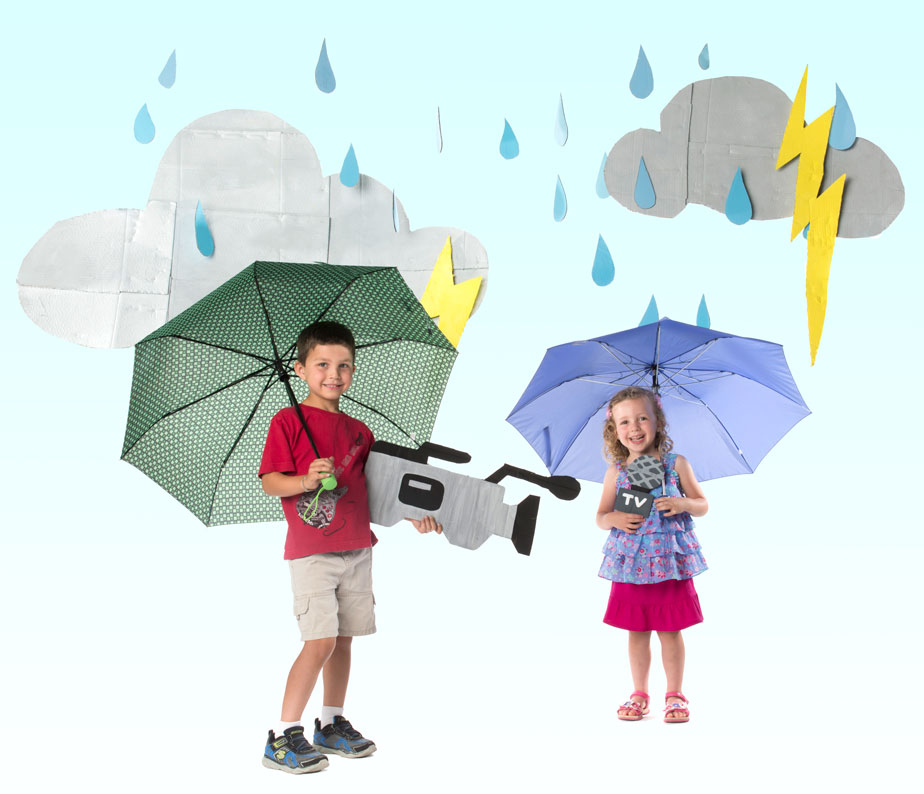 Photo of two children holding umbrellas in cut-outs of rain clouds, rain, and camera