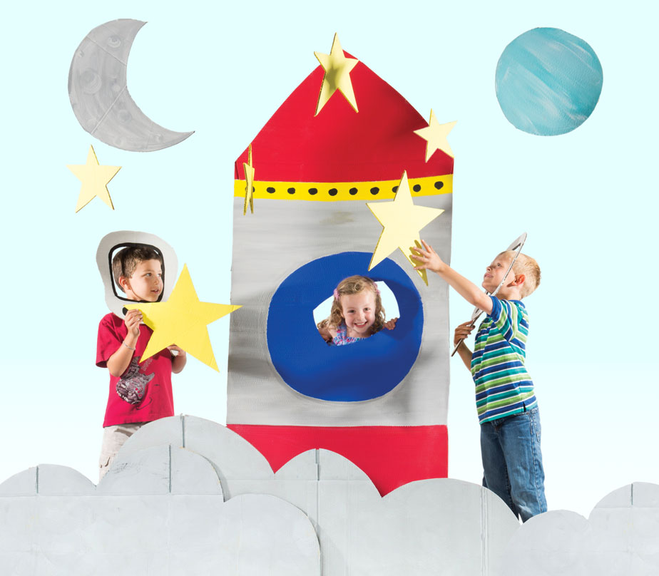Photo of three children playing with cut out rocket, stars, and planets