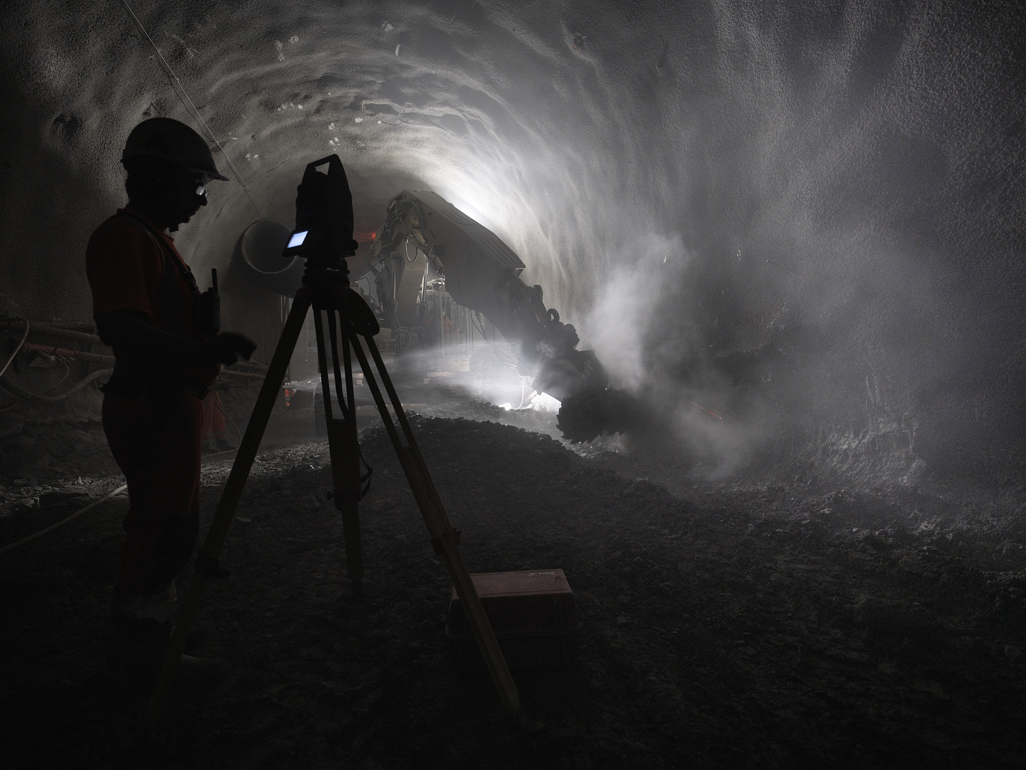 Silhouette of person in construction helmet in dimly lit tunnel