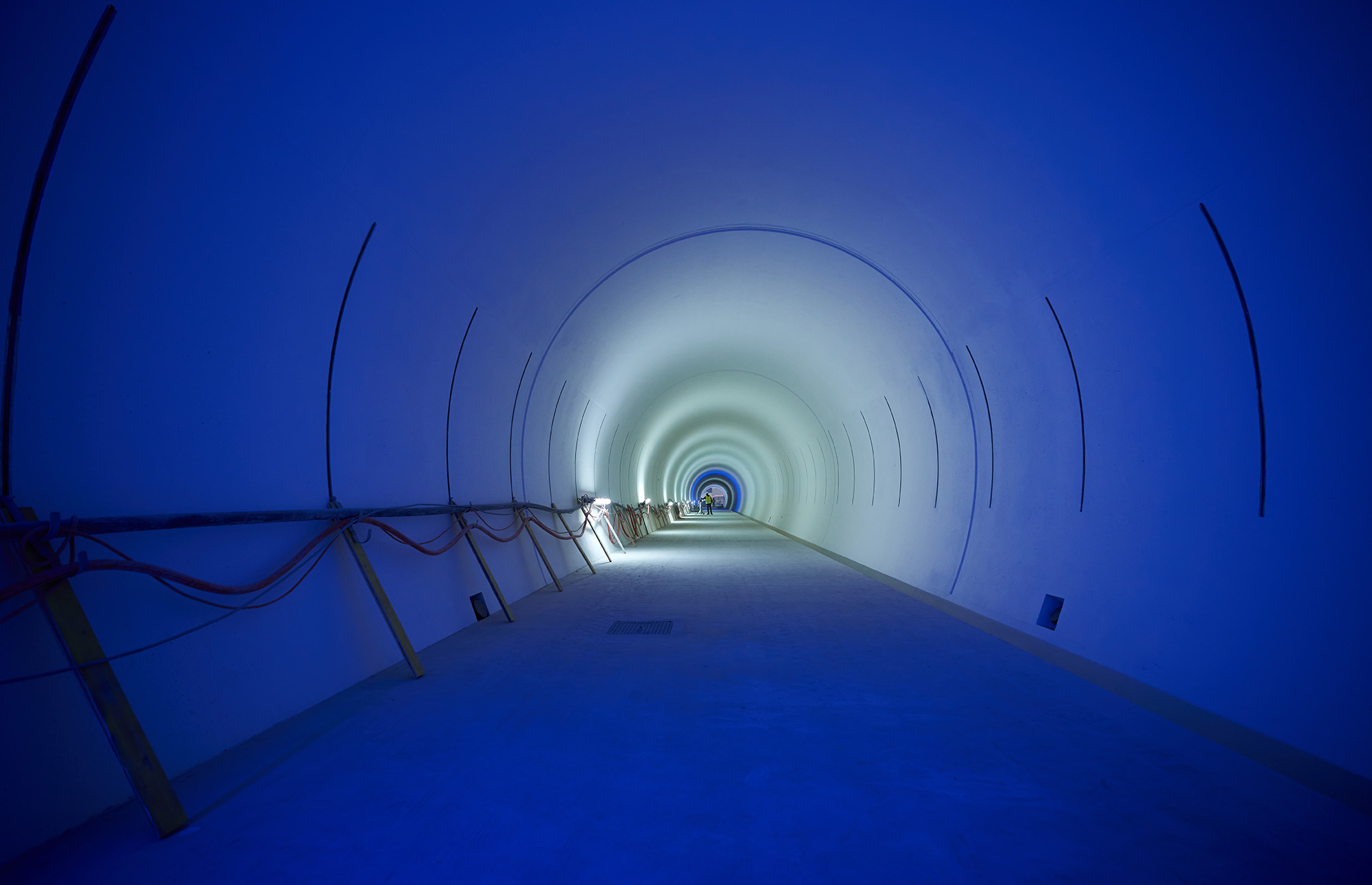 Clean, white tunnel illuminated by blue lights