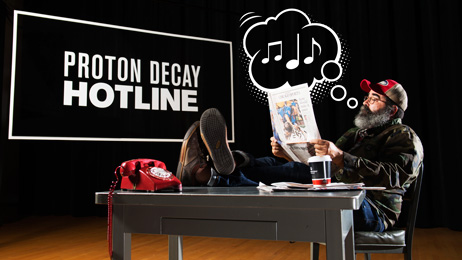Proton decay hotline, man sits at desk with old red dial phone on desk and musical notes coming out of his mouth