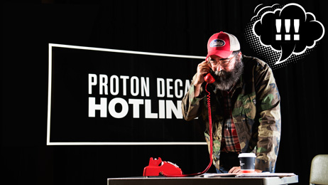 "Proton decay hotline, man answering old red dial phone with ""!!!"""