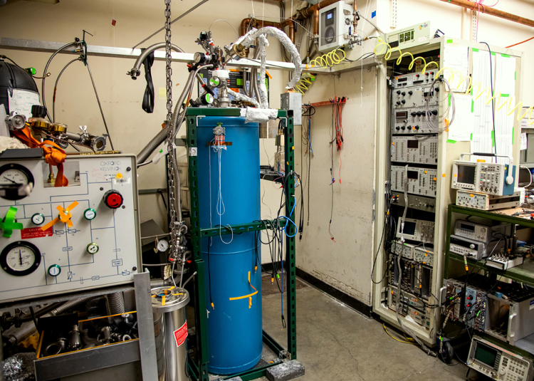 Photo of a tall blue tank in a room full of experimental equipment