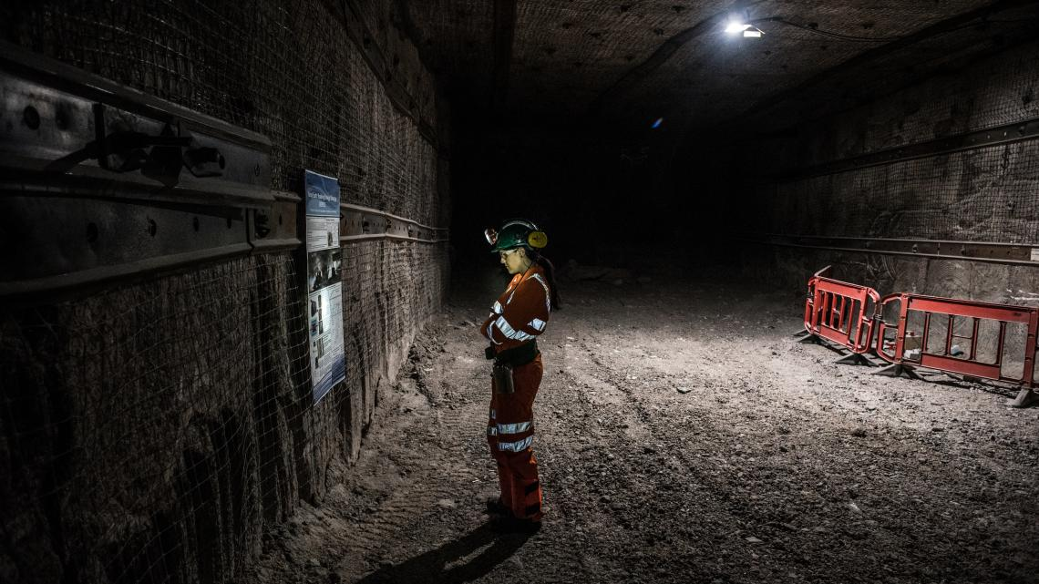 Scientist standing in a mine tunnel, reading a sign, with her face lit by a headlamp on her helmet