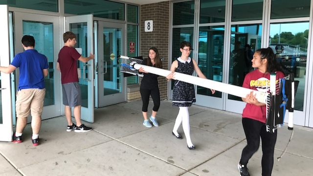 Photo of three students carrying a long detector while another holds the door