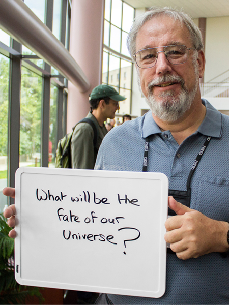 "Photo of Steve Wimpenny holding whiteboard that says ""What will be the fate of the universe?"""