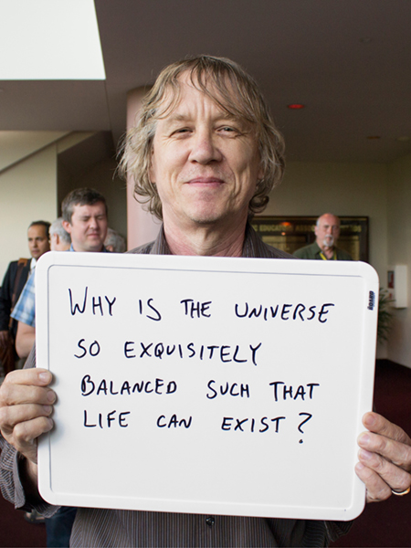 "Photo of Erik Ramberg holding whiteboard that says ""Why is the universe so exquisitely balanced such that life can exist?"""