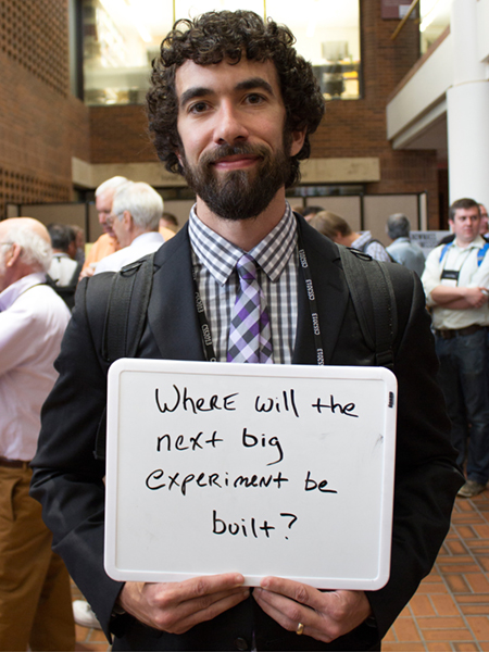"Photo of Jonathan Asaadi holding whiteboard that says ""Where will the next big experiment be built?"""