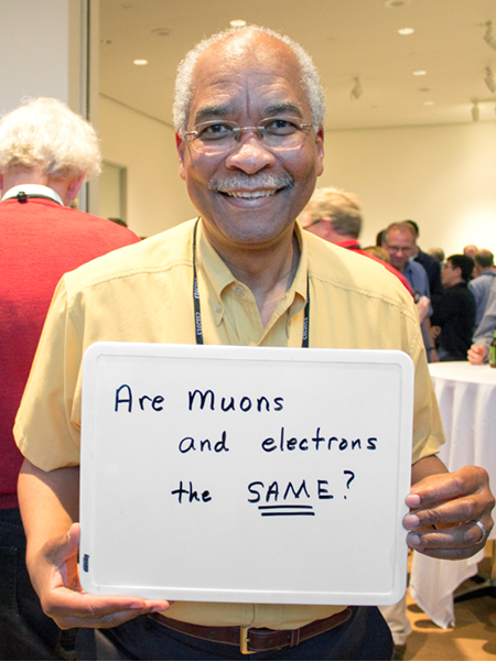 "Photo of Herman White holding whiteboard that says ""Are muons and electrons the same?"""