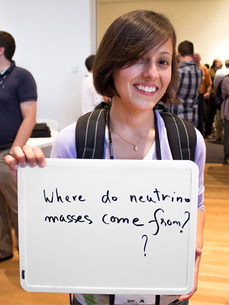 "Photo of Kanika Sachdev holding whiteboard that says ""Where do neutrons masses come from?"""