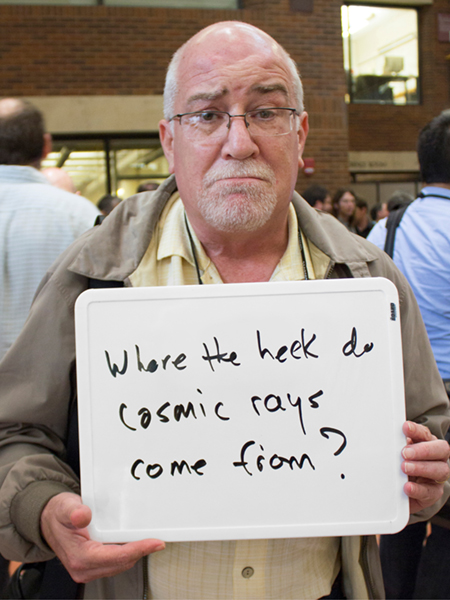 "Photo of James Matthews holding whiteboard that says ""Where the heck do cosmic rays come from?"""