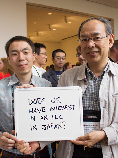 "Photo of Akiya Miyamoto and Hiroaki Ono holding whiteboard that says ""Does US have interest in an ILC in Japan?"""