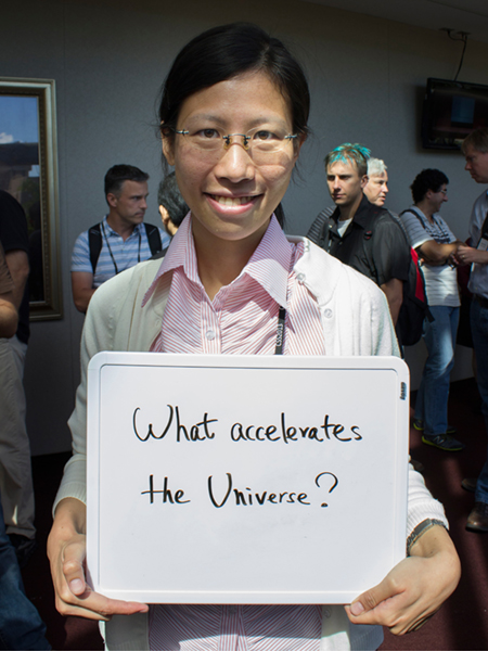 "Photo of Hao-Yi Wu holding whiteboard that says ""What accelerates the universe?"""