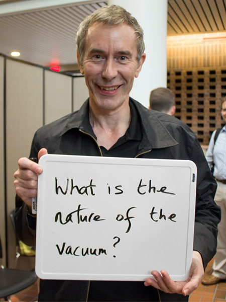 "Photo of Ian Shipsey holding whiteboard that says ""What is the nature of the vacuum?"""