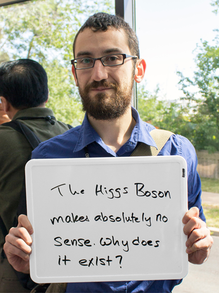 "Photo of Richard Ruiz holding a whiteboard that says ""The Higgs Boson makes absolutely no sense. Why does it exist?"""