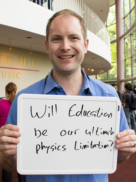 "Photo of Wade Fisher holding a whiteboard that says ""Will education be our ultimate physics limitation?"""