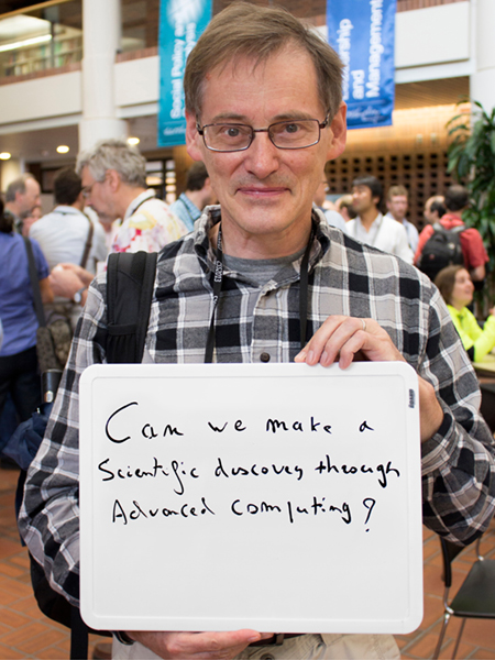 "Photo of Paul Lebrun holding a whiteboard that says ""Can we make a scientific discovery through advanced computing?"""