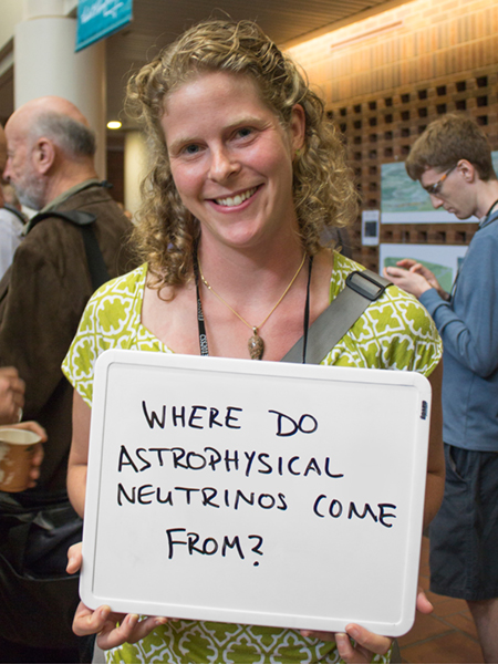 "Photo of Abigail Vieregg holding whiteboard that says ""Where do astrophysical neutrinos come from?"""