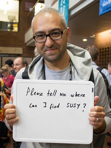 "Photo of Altan Cakir holding whiteboard that says ""Please tell me where can I find SUSY?"""