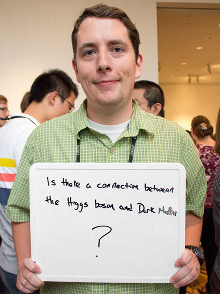 "Photo of Gabe Shaughnessy holding whiteboard that says ""Is there a connection between the Higgs boson and Dark Matter?"""