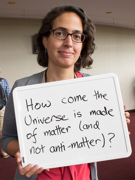 "Photo of Alysia Marino holding whiteboard saying ""How come the universe is made of matter (and not anti-matter)?"""
