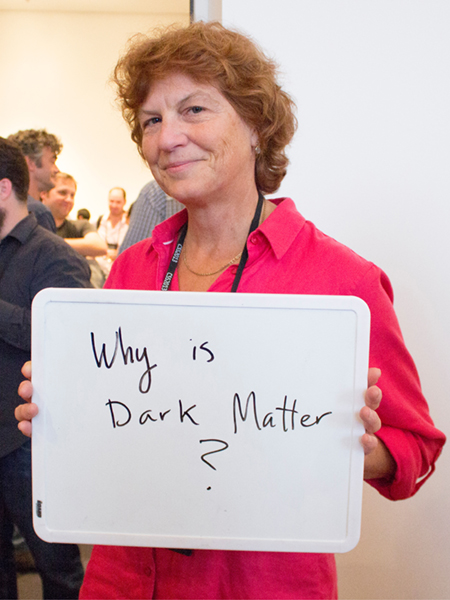 "Photo of Prisca Cushman holding whiteboard saying ""Why is Dark Matter?"""