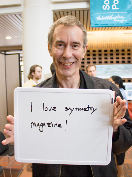 "Photo of man holding a whiteboard that says ""I love symmetry magazine"""