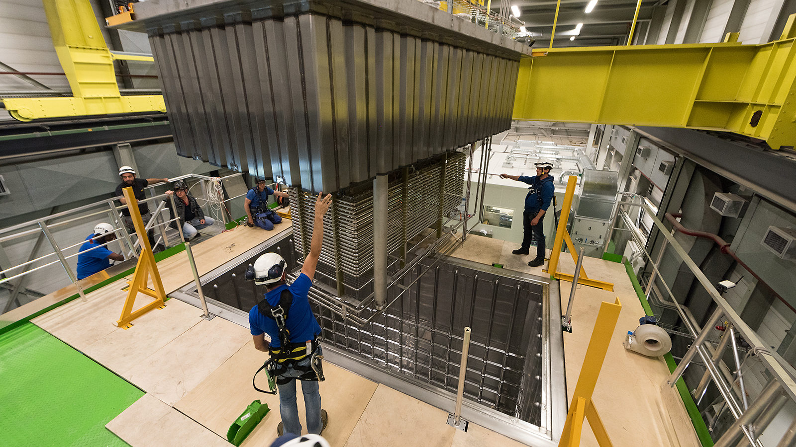 People in hard hats install the 311 detector