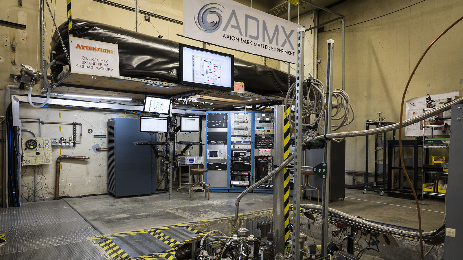 Photo of equipment and panels for the ADMX experiment fill the room: an ADMX experiment banner hangs above