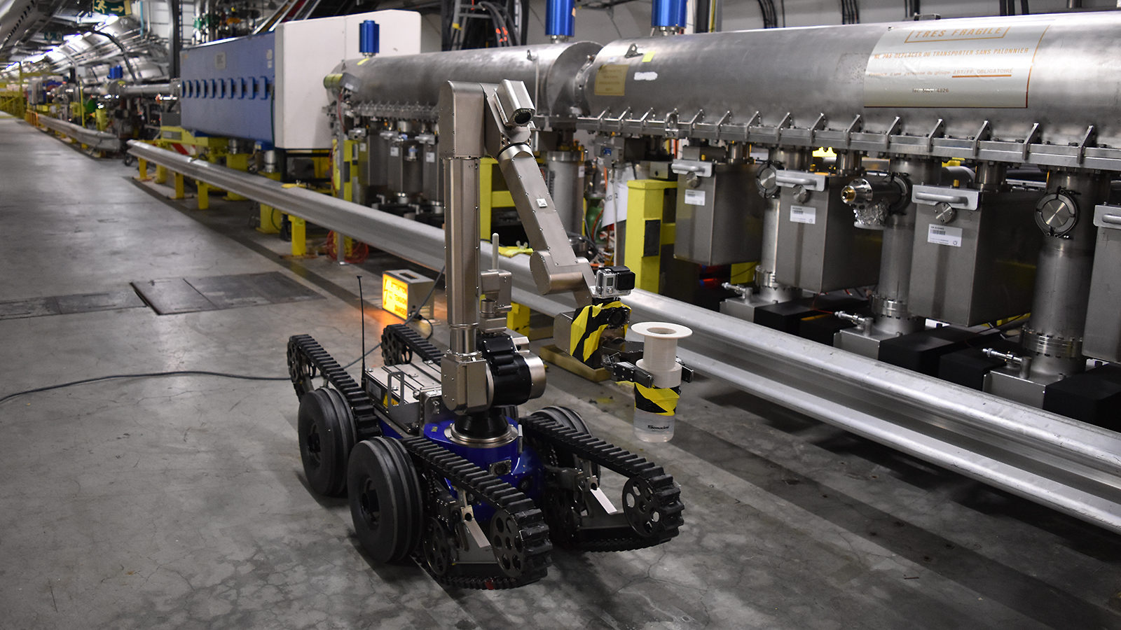 Robot with wheels, an arm and a camera in the tunnel of the Large Hadron Collider