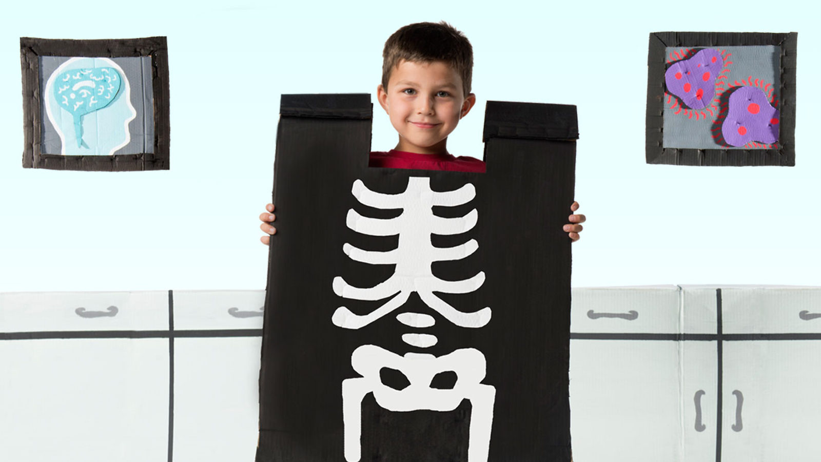 Photo of child holding a cut-out of an X-ray of his skeleton over his body