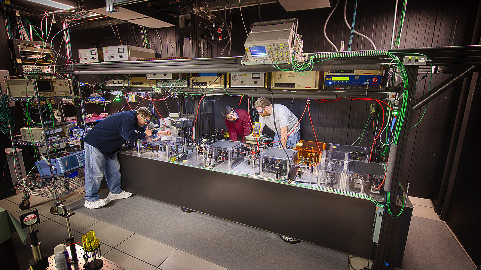Scientists in laser safety goggles work in a laser lab
