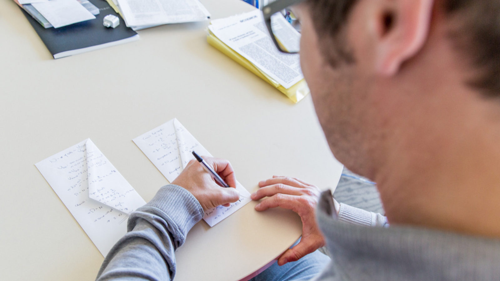 Photo of man writing on back of the envelopes