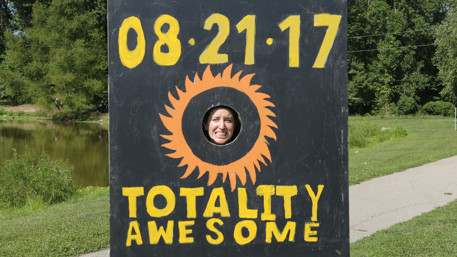 "Photo of woman putting her face through wood cut out that says ""08.21.17 Totality Awesome"" for great eclipse"