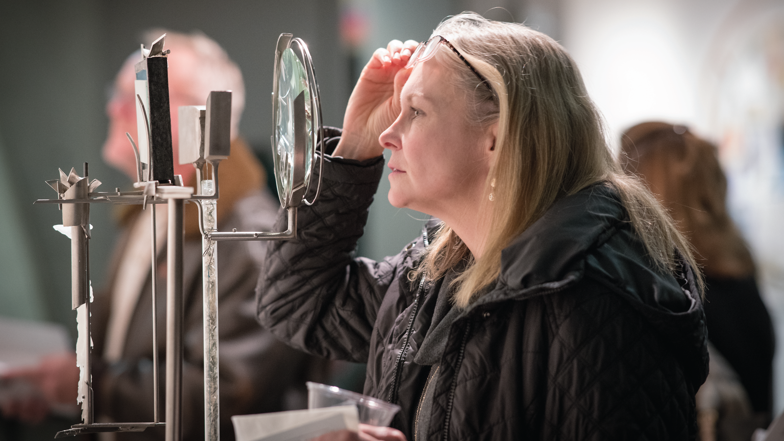 Photo at the artist's reception for Jenkins' show, a visitor peers through the magnifying glass of a sculpture