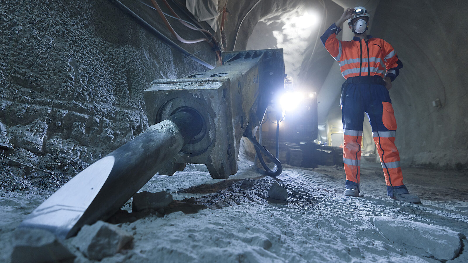 Photographer Samuel Hertzog, in an orange construction-site uniform, stands among heavy equipment in the tunnel