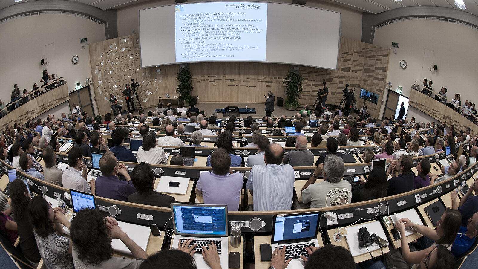Photo from the back of a crowded conference room on the day of the Higgs announcement