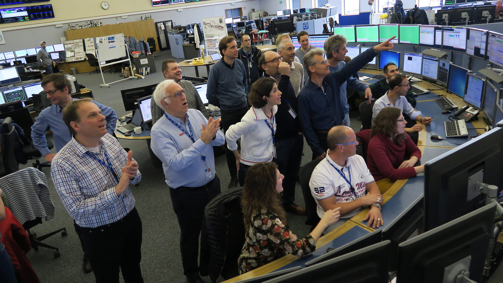 Photo accelerator operators and CERN's Director General stand together watching the process of the LHC beam on a computer screen