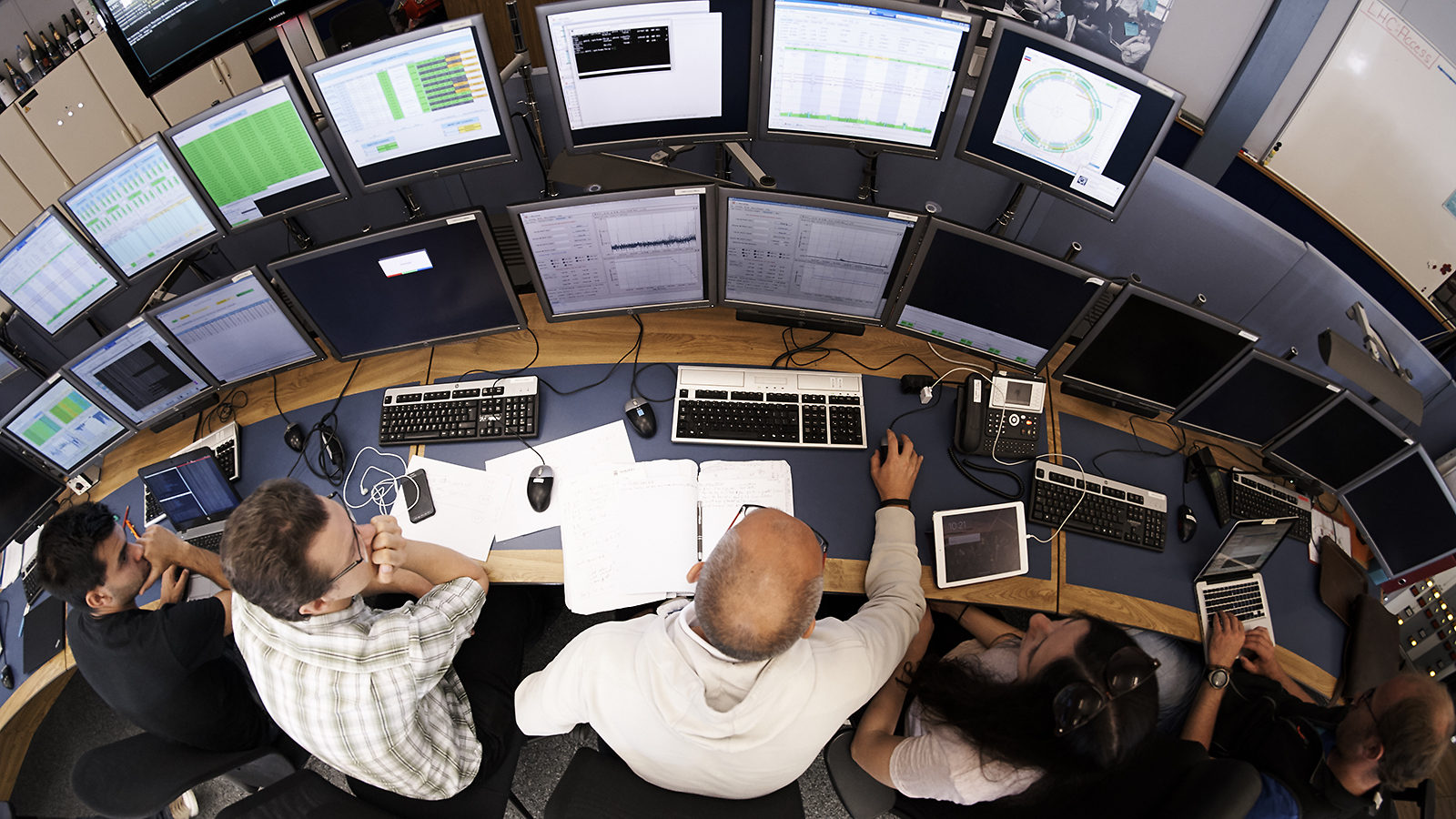 Overhead view of people sitting in front of two rows of computer screens