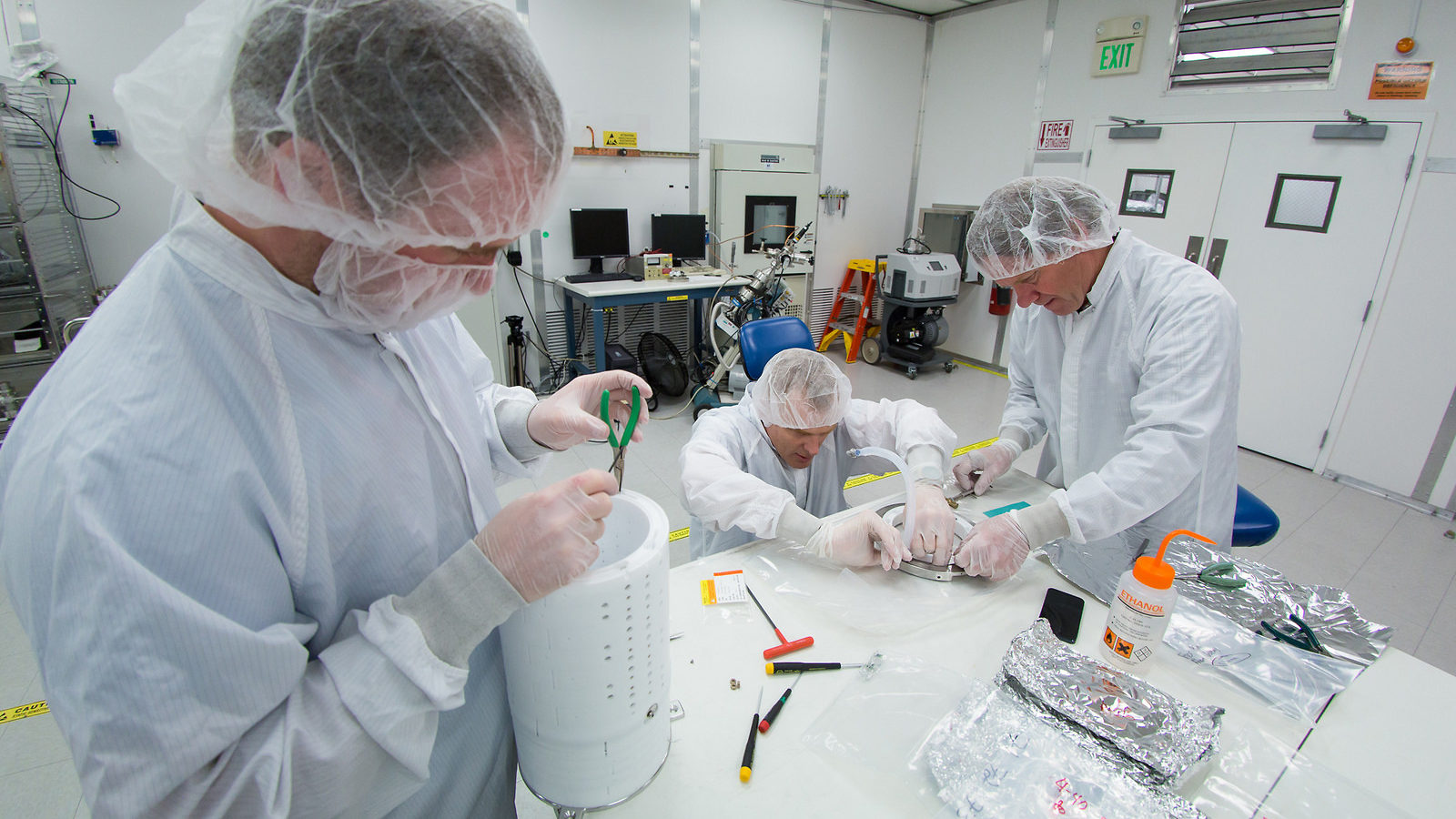 Scientists in a cleanroom assemble the prototype for the LZ detector's core.