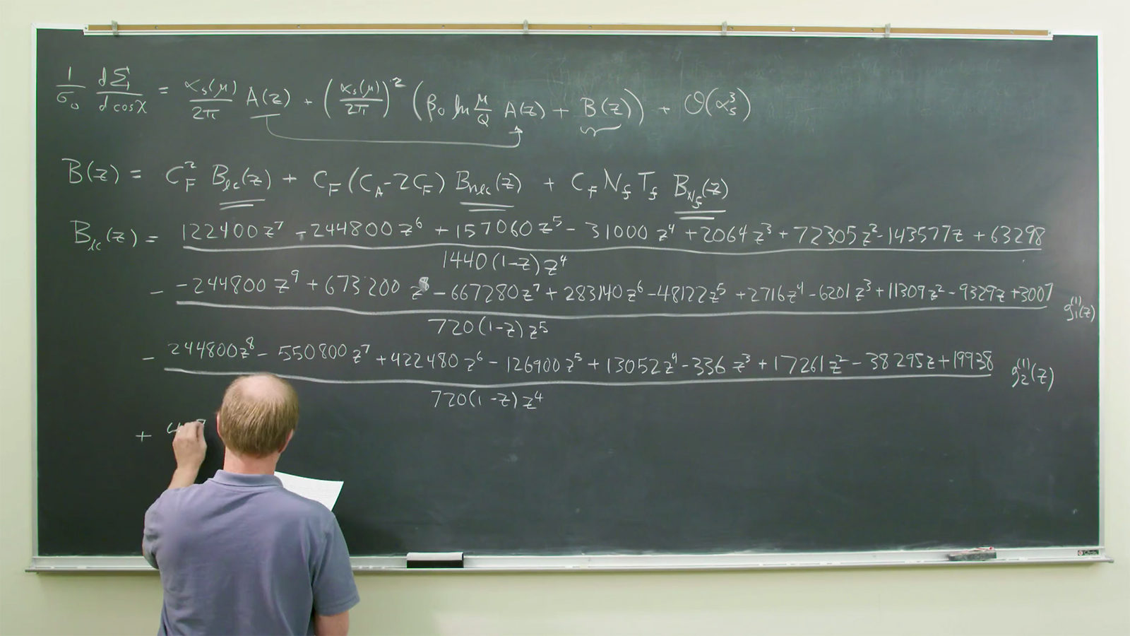 Video still showing theorist Lance Dixon writing on a large chalkboard