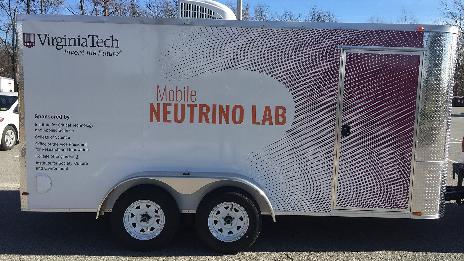 """White trailer with the words """"Mobile Neutrino Lab"""" on the side"""