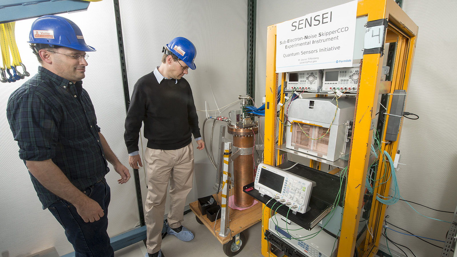 Two scientists in hard hats stand next to a cart holding detector components.