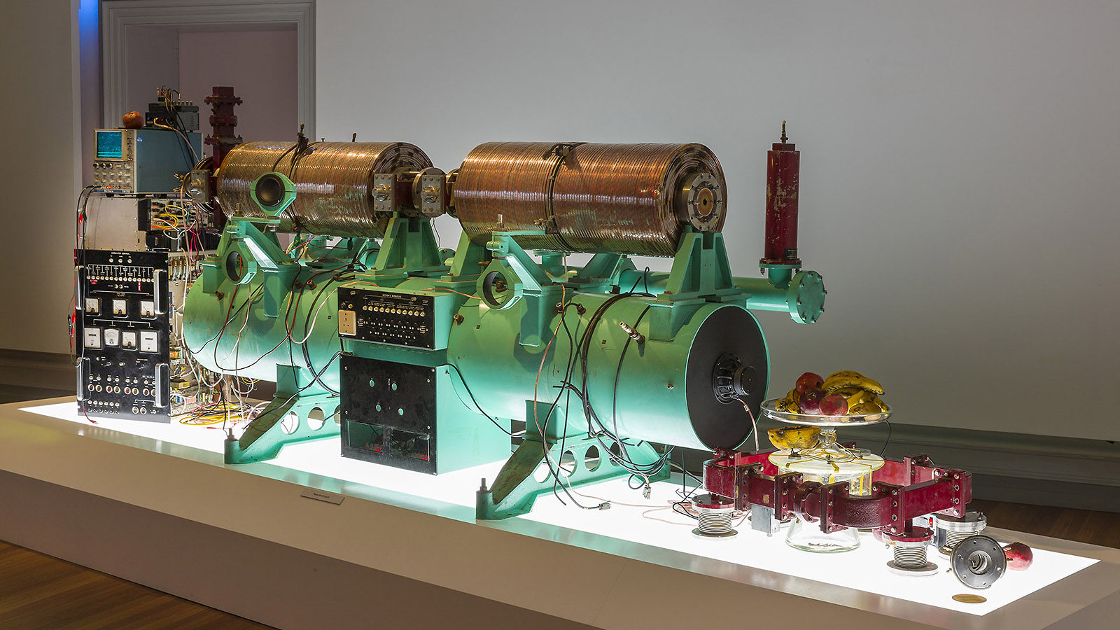 Green piece of an accelerator machinery and a plate of fruit on a lit table